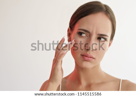 beauty portrait of sad woman touching her skin on white background  #1145515586