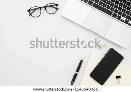 Flat lay photo of office desk with laptop, smartphone, eyeglasses and notebook with copy space background. Mockup