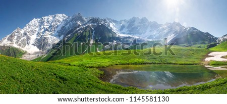 Mountain landscape of Svaneti on bright summer sunny day. Mountain lake, hills covered green grass on snowy rocky mountains background. Caucasus peaks in Georgia. Amazing view on wild georgian nature #1145581130