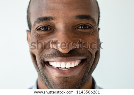 Happiness inside. Close up of joyful handsome adult afro american man smiling against white background #1145586281