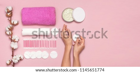 Spa concept. Cotton pads for removal makeup with woman hands, cotton branch, cotton pads, ear sticks, pink towel. Cotton Cosmetic Makeup Removers Tampons. Flat lay background Top view copy space #1145651774