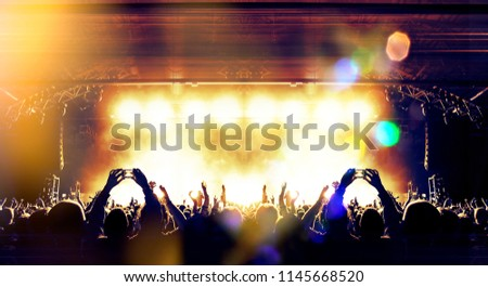 Concert crowd attending a gig in a night venue #1145668520