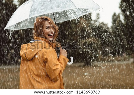 Cheerful pretty girl holding umbrella while strolling outside. She is turning back and looking at camera with true delight and sincere smile. Copy space in right side #1145698769