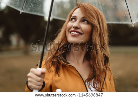 Waist up portrait of delighted female holding umbrella outside. She is watching upwards with curious and dreaming look #1145698847
