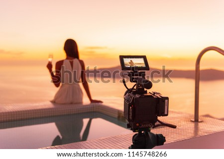 Video camera filming actress woman acting for movie on luxury hotel location behind the scenes of shoot. Professional videography equipment shooting outdoor at sunset. #1145748266