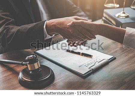Judge gavel with Justice lawyers having team meeting at law firm background. Concepts of Law and Legal services. #1145763329