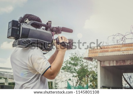 Covering an event with a video camera., Videographer takes video camera., Video cameran operate working at the street. #1145801108
