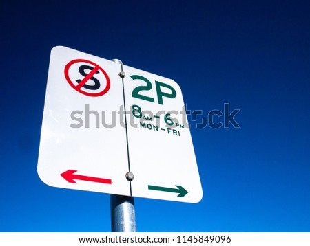 Australian street parking sign against blue sky. 2P indicates only 2 hour parking time allowed between 8am to 6pm Monday to Friday. No restriction on the other times. Melbourne, Victoria.