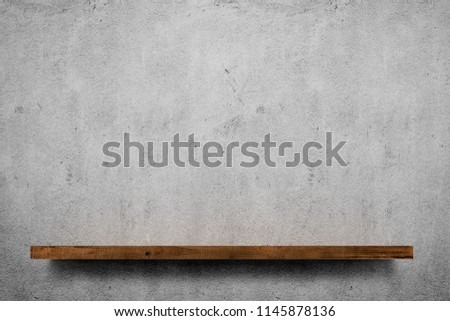 Wooden shelf over grey concrete wall background Royalty-Free Stock Photo #1145878136
