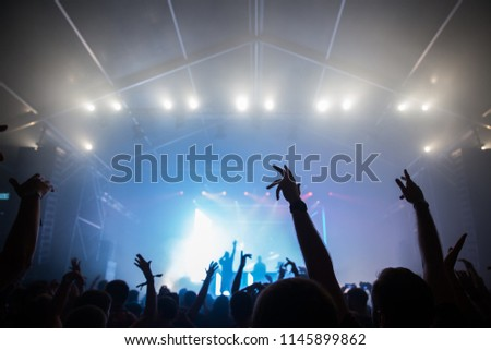 Stage lights and crowd of audience with hands raised at a music festival. Fans enjoying the summer vibes. #1145899862