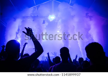 Stage lights and crowd of audience with hands raised at a music festival. Fans enjoying the summer vibes. #1145899937
