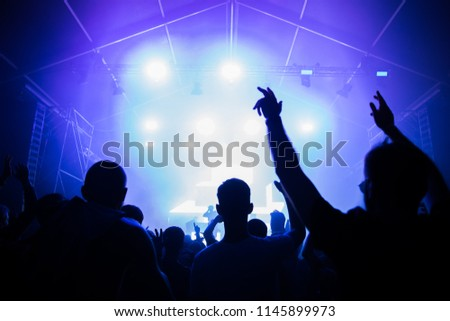 Stage lights and crowd of audience with hands raised at a music festival. Fans enjoying the summer vibes. #1145899973