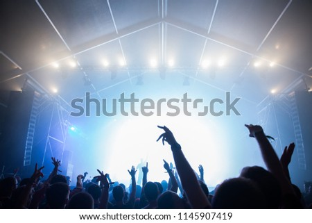 Stage lights and crowd of audience with hands raised at a music festival. Fans enjoying the summer vibes. #1145907419