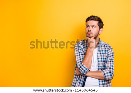 Close up portrait of thoughtful man who looks away touching his chin and weighs the pluses and minuses of the offer isolated on bright yellow background with copy space for text #1145964545
