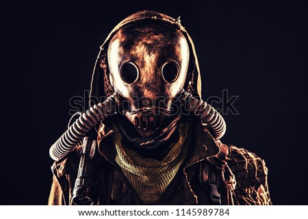 Close up portrait of nuclear post-apocalypse survivor, living underground mutant or creature, skilled stalker wearing rags and armored full-face gas mask or air breathing apparatus, toned shoot #1145989784