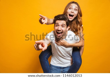 Image of caucasian man and woman sitting on his back pointing fingers aside at copyspace isolated over yellow background #1146012053