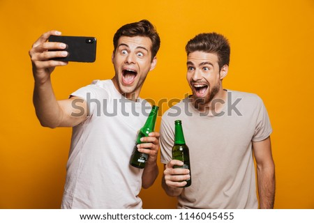 Portrait of a two happy young men best friends taking a selfie while holding beer bottles and shouting isolated over yellow background