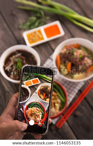 gesture of hand taking picture of delicious traditional food. blogger concept #1146053135