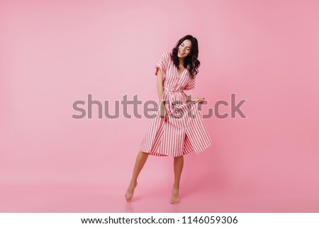 Shapely barefooted lady with tanned skin dancing on pink background. Happy caucasian girl in striped dress fooling around and laughing. Royalty-Free Stock Photo #1146059306