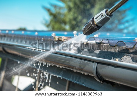 Spring Rain Gutters Cleaning Using Pressure Washer. Closeup Photo. Royalty-Free Stock Photo #1146089963