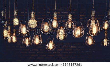 Beautiful vintage luxury light bulb hanging decor glowing in dark. Retro filter effect style. #1146167261