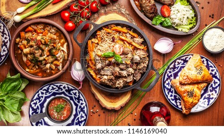Traditional Uzbek oriental cuisine. Uzbek family table from different dishes for the New Year holiday. The background image is a top view. #1146169040