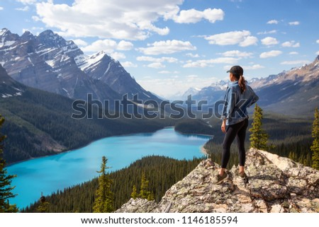 Young girl enjoying the beautiful Canadian Rockies Landscape view during a vibrant sunny summer day. Taken in Peyto Lake, Banff National Park, Alberta, Canada. #1146185594