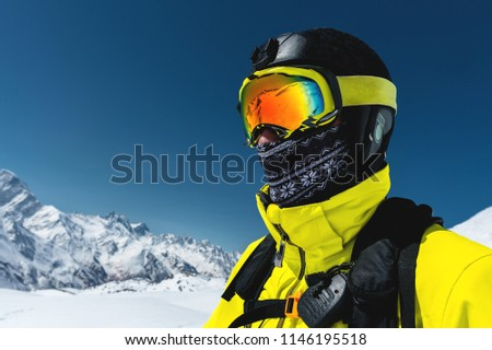 Close-up portrait of a skier in a mask and helmet with a closed face against a background of snow-capped mountains and blue sky #1146195518