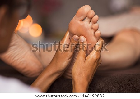 Closeup of masseuse doing foot reflexology to woman at spa. Therapist hands doing foot massage at wellness center. Woman receiving a feet massage at health spa. #1146199832