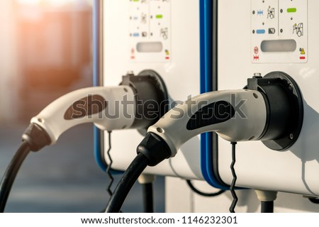 Electric car charging station. Plug for vehicle with electric motor. Coin-operated charging station. Clean energy power. Commercial charging station. Charging point. Infrastructure policy.  #1146232301