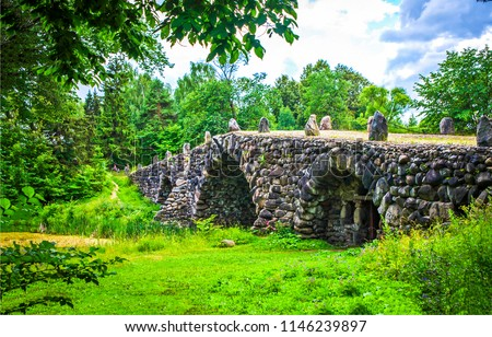 Ancient stone bridge in deep forest landscape. Stone bridge in deep forest scene. Medieval stone bridge view #1146239897
