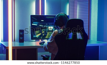 Beautiful Professional Gamer Girl Playing in First-Person Shooter Online Video Game on Personal Computer. Casual Cute Geek Girl Wearing Headset. Dark Room Suddenly Lit by Neon Lights in Retro Style #1146277850