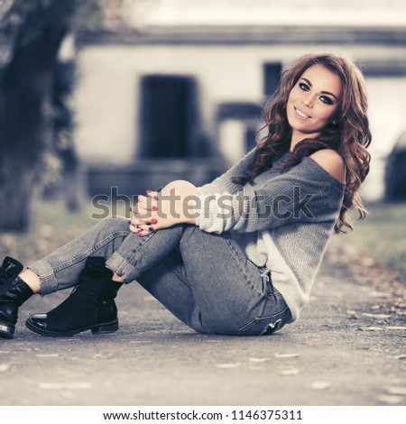 Happy young fashion woman sitting on sidewalk Stylish female model wearing ripped jeans and grey pullover #1146375311