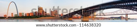 Wide panoramic view of St Louis downtown including the Arch and Eads Bridge train crossing spanning the Mississippi river