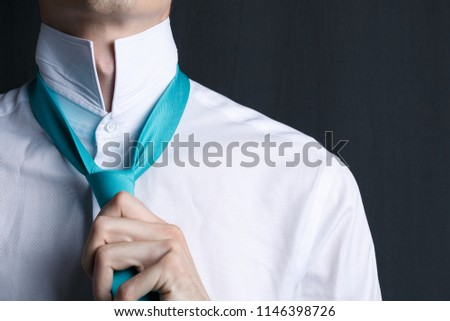 Close-up young man in a white shirt with a tie. The man straightens his tie, his face unshaven. Businessman in a white shirt and turquoise necktie. Dark background. Copy space #1146398726