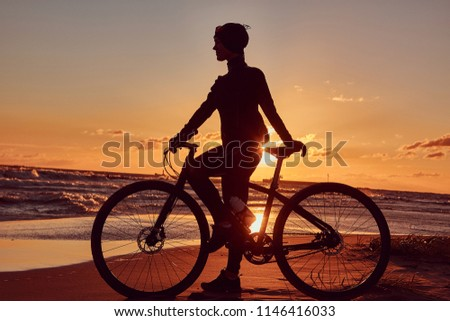 Female cyclist standing with her bicycle and enjoying the sunset on the sea coast. #1146416033