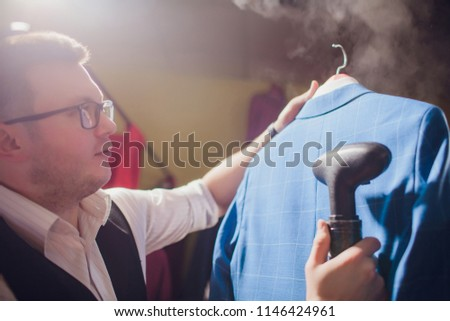 tailor cuts and sews a suit. A young man in the tailoring shop makes men's clothing. Custom-made clothing workshop. holds in her hand an electric iron. wet-heat treatment #1146424961
