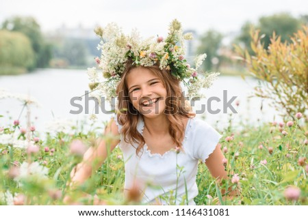 Beautiful blonde girl in a field in a wreath, smiling and laughing. concept of a happy summer. Teenager is happy #1146431081