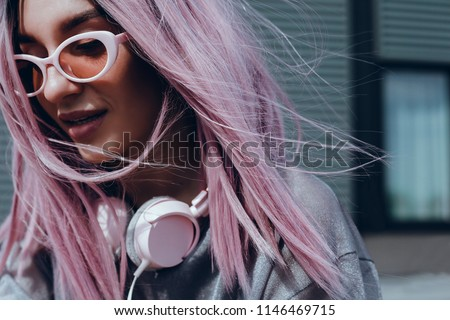 Beautiful young girl with purple pink hair listening to music on headphones, street style, outdoor portrait, hipster girl, music, mp3, Bali, beauty woman, sunglasses, orange color, concept #1146469715