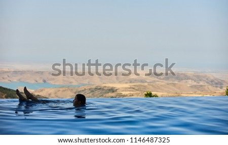 Young Woman tourist in infinity pool of hotel resort enjoying the view over the ocean #1146487325