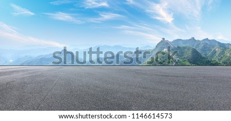 Empty asphalt road and great wall with mountains under the blue sky #1146614573