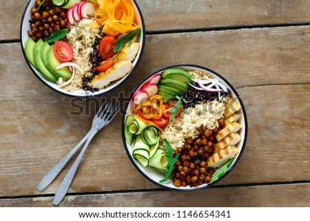 Two buddha bowl. Clean and balanced healthy food concept. Chicken grilled steak, rice, spicy chickpeas, black and white quinoa, avocado, carrot, zucchini, radish, tomatoes on wooden table top view #1146654341