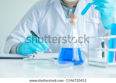 Medical science or male Compiling an Analysis Report in laboratory room research performs tests with blue liquid on test tube, Experimental Drug Treatment Chemicals #1146720452