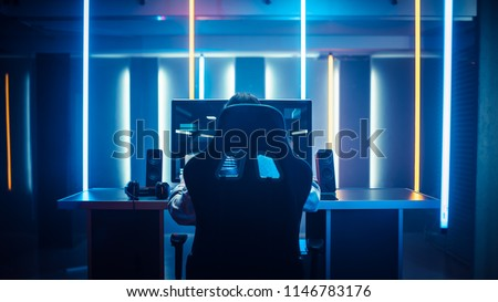 Professional Gamer Playing in First-Person Shooter Online Video Game on His Personal Computer. Room Lit by Neon Lights in Retro Arcade Style. Cyber Sport Championship. #1146783176