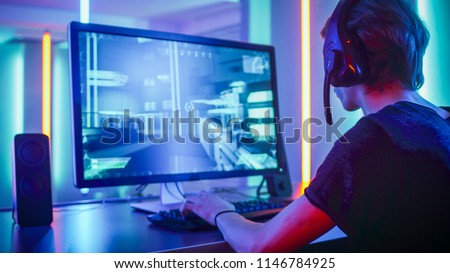 Shot of the Professional Gamer Playing in First-Person Shooter Online Video Game on His Personal Computer. Room Lit by Neon Lights in Retro Arcade Style. Online Cyber e-Sport Internet Championship. #1146784925