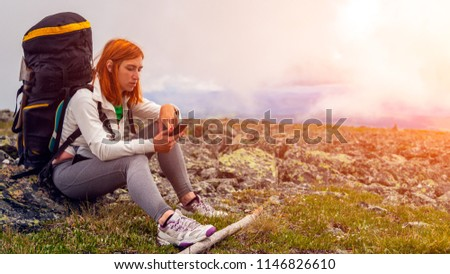 Travel Lifestyle and survival concept rear view. Hiking women  with backpack  are very tired and sit on rock and look at phine, enjoying the trekking, in the background  mountains.  #1146826610