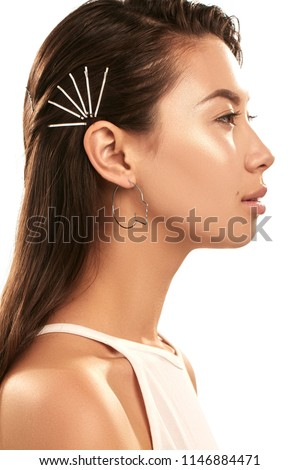 Close up studio portrait of a young Asian lady wearing abstract face-shaped hoop earrings. The side view of the brunette girl with slicked back hair with bobby pins, posing over the white background. #1146884471