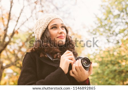 Young beautiful woman with a woolen cap taking pictures with a retro camera in the city in autumn #1146892865