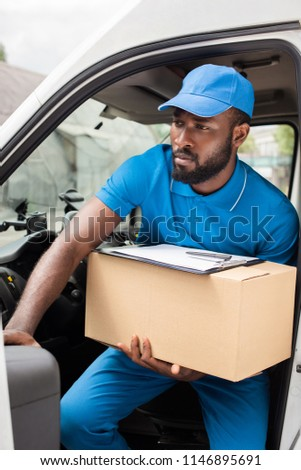 african american delivery man going out from car with box #1146895691