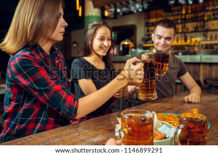 The people, leisure, friendship and communication concept - happy friends drinking beer, talking and clinking glasses at bar or pub #1146899291